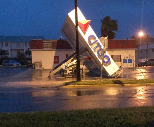 Broken gas station sign on ground due to storm damage